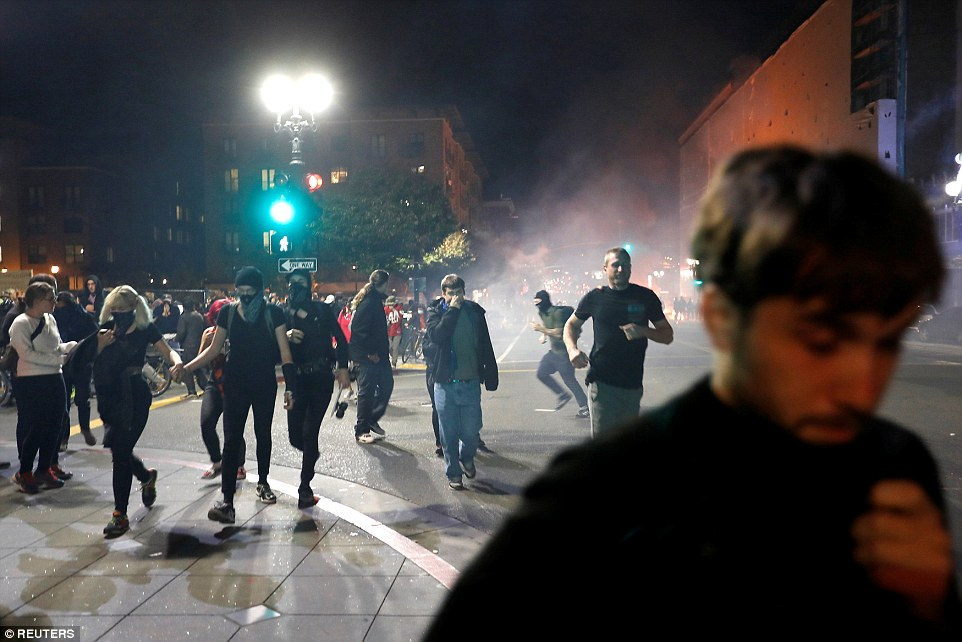 Oakland: Demonstrators run on Telegraph Avenue after police deployed teargas during a demonstration in the city