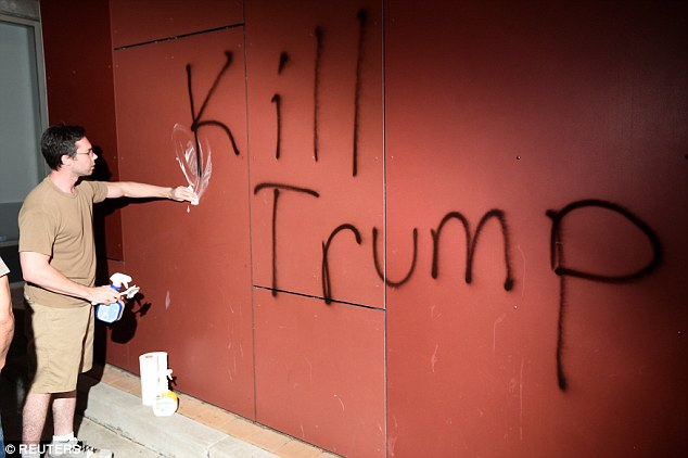 A man tries to remove 'Kill Trump' graffiti as demonstrators riot in Oakland, California