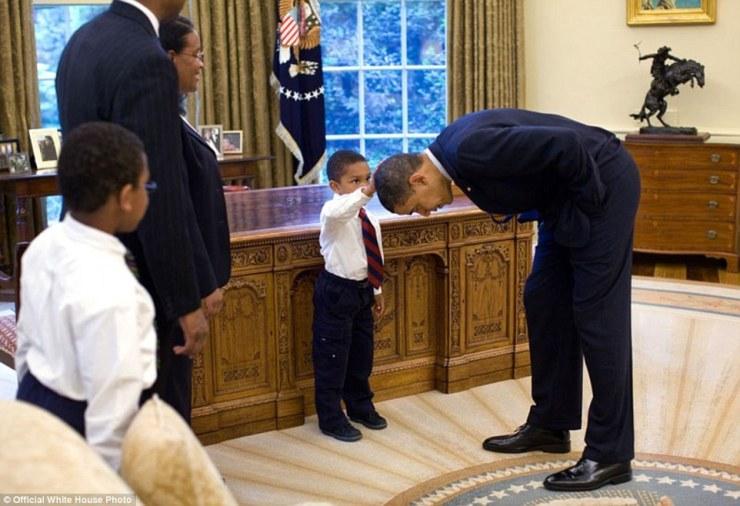8 mai 2009. Obama se penche sur de sorte que le fils d'un membre du personnel de la Maison Blanche peut caresser la tête lors d'une visite dans le bureau ovale