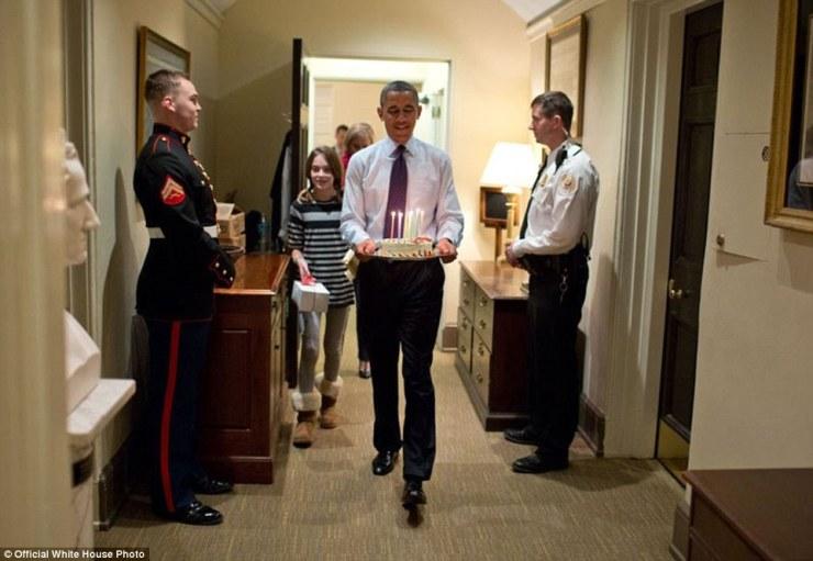 Le président Barack Obama, rejoint par le chef de la fille du major Denis McDonough, porte un gâteau d'anniversaire pour surprendre McDonough dans son bureau West Wing, le 2 Décembre, 2013