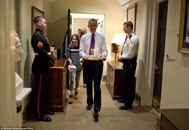 President Barack Obama, joined by Chief of Staff Denis McDonough's daughter, carries a birthday cake to surprise McDonough in his West Wing office, on December 2, 2013