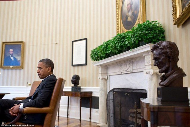 September 28, 2012. 'A candid portrait of the President during a meeting, juxtaposed with the paintings of Abraham Lincoln and George Washington, busts of Martin Luther King, Jr., and Abraham Lincoln, and the Emancipation Proclamation. It's a difficult angle to get because I had to sit in front of the closed Oval Office door and hope that no one would open the door and knock me over'