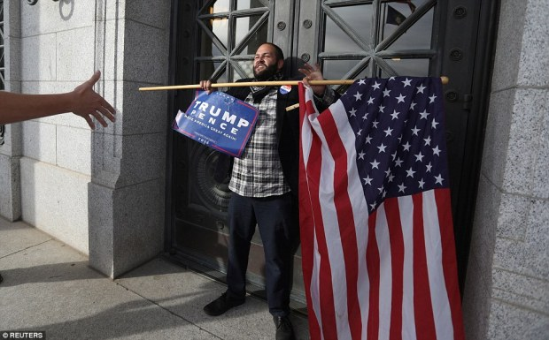 Donald Trump supporter Kern Carlos Huerta stands in front of the Utah State Capitol building doors as demonstrators protest against the election of Republican nominee