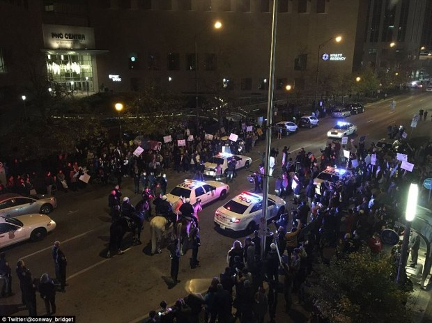 Crowds of people are seen on both sides of the street outside a hotel in downtown Indianapolis during anti-Trump protests on Saturday night