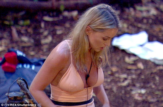 Getting down to business:The star set up her bed in the raunchy dress - flashing her bust through the saucy low-cut neckline as she bent down to undo her sleeping bag