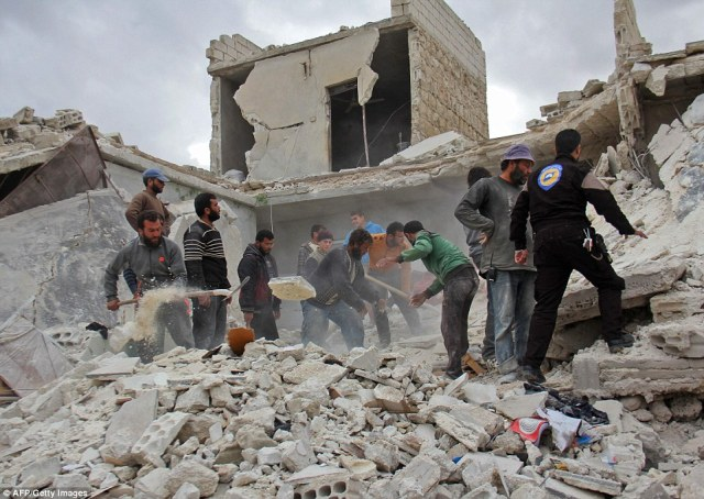 Rescuers and civilians inspect a destroyed building in the Syrian village of Kfar Jales, on the outskirts of Idlib, following air strikes by Syrian and Russian warplanes on November 16