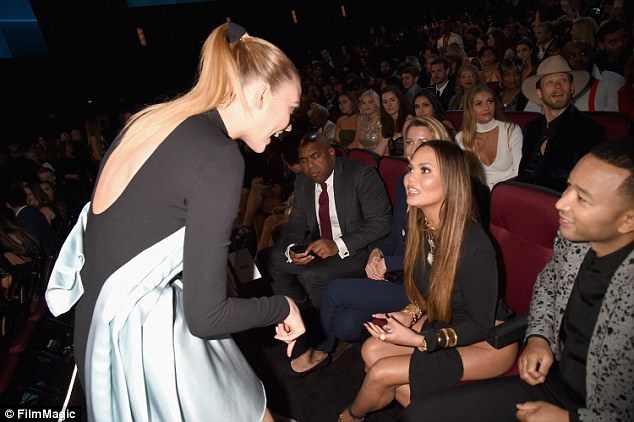 Having a quick chat: The lovebirds were snapped talking with model Karlie Kloss, who walked over to their seats to greet them
