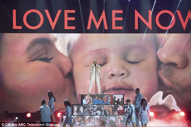 Sweet kisses: While he sang, images of himself, Chrissy and daughter Luna appeared behind him on the big screen
