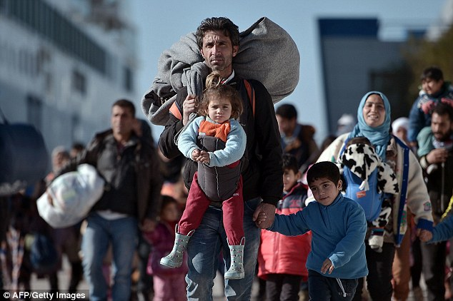 Thousands of migrants and refugees walk through the port of Piraeus after arriving from the Greek islands of Lesbos and Chios in February this year