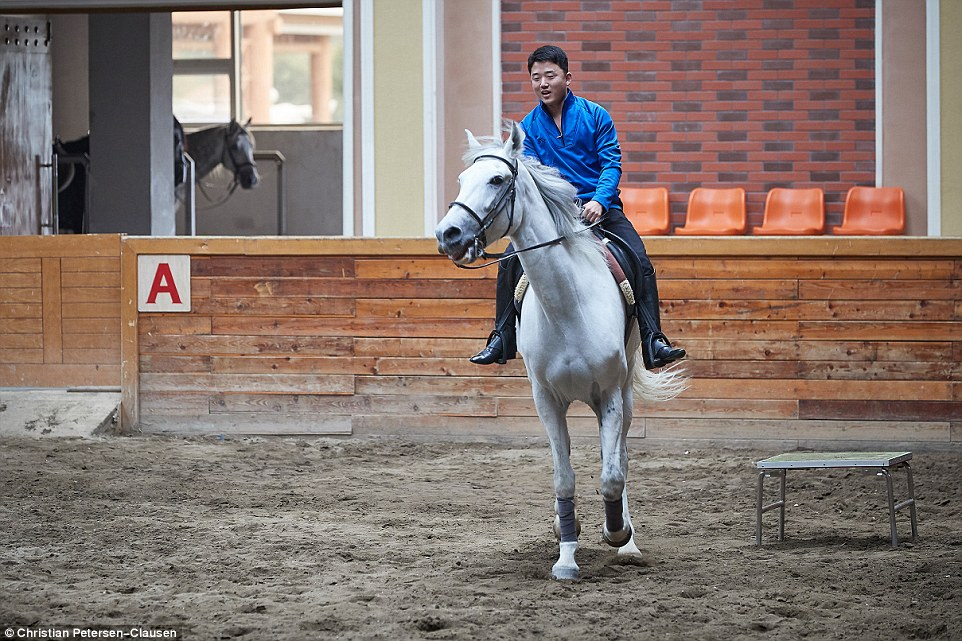 These entrepreneurs and their families and friends make up around 10 per cent of the country's population and they are an elite that the regime turns a blind eye to. Above, a North Korean takes a horse riding lesson