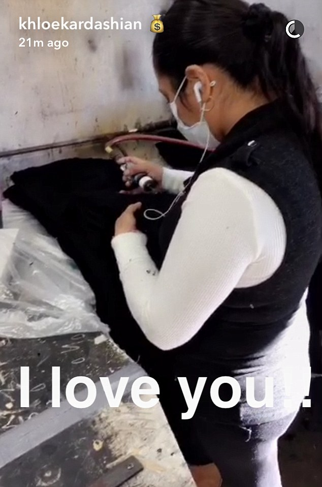 All by hand: Khloe went to the next station where a worker was putting the rips in the jeans'
