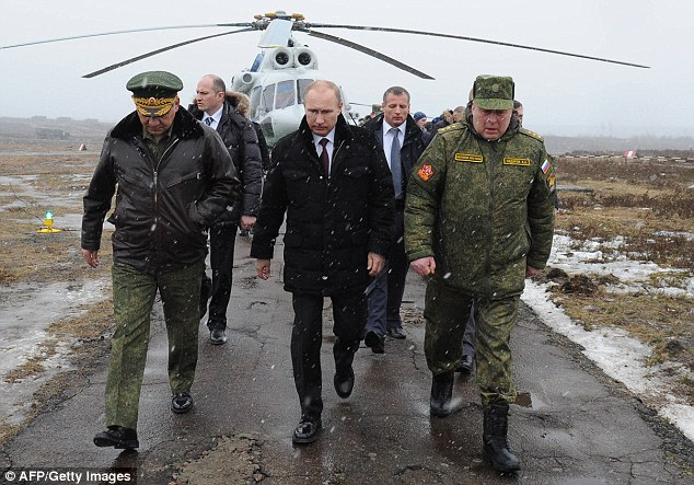 Russia's President Vladimir Putin (front centre) and his then defence minister Sergei Shoigu (front left) walk to watch military exercises upon his arrival at the Kirillovsky firing ground in the Leningrad region, on March 3, 2014