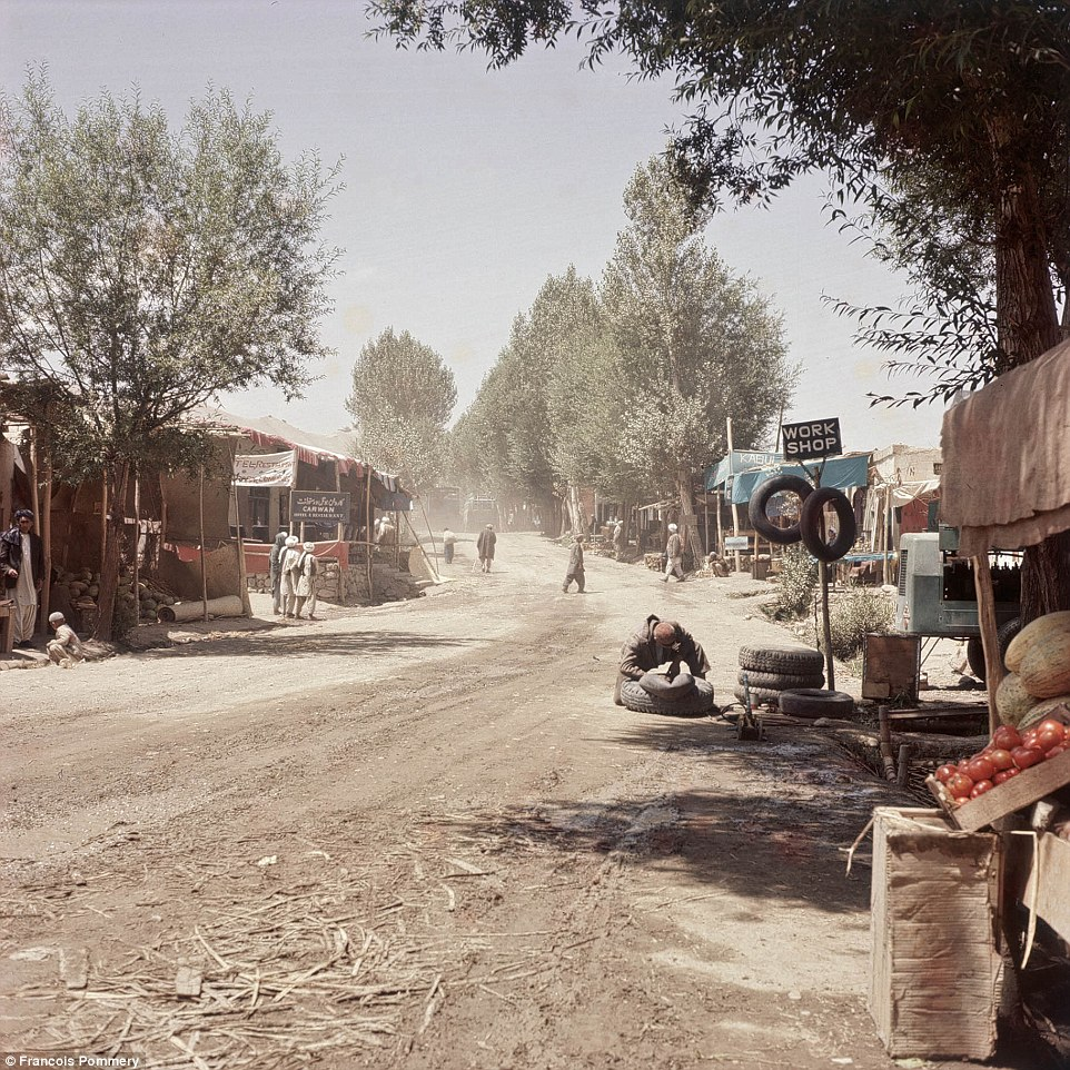 A repair workshop on a dusty road in Bamiyan. The scene is an idyllic one, with fresh fruit for sale and lush trees lining the route