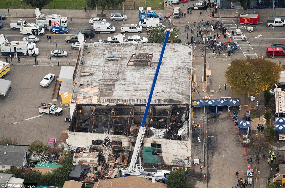 Devastating aerial photos show the aftermath of the deadly inferno that took place at an Oakland warehouse during a party Friday night, as prosecutors launch an investigation that could lead to murder charges. A crane (pictured) was being used to lift wreckage as part of continued search efforts on Monday