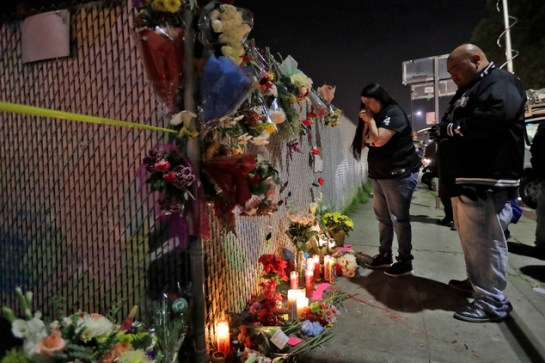 Sol Rodriguez, center, and Aaron Torres visit a shrine for the victims of a warehouse fire near the site Sunday, Dec. 4, 2016, in Oakland, Calif. The death t...