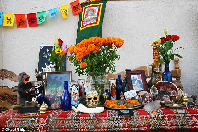 Mixed-up: A typical display from the Ghost Ship's website showed how elements of Christianirt (the candles) were mixed with an apparent Buddhist prayer flag (top peft) and Hindu items (the garland and the larger flag)