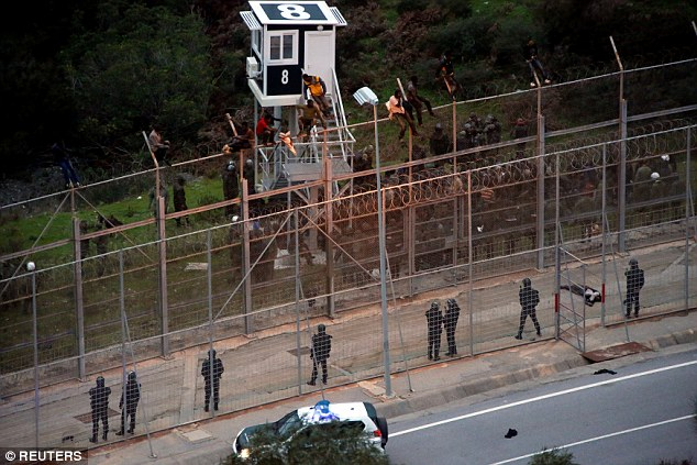 African migrants sit on top of a border fence during an attempt to cross into Spanish territories, between Morocco and Spain's north African enclave of Ceuta today