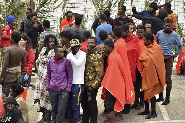 Migrants stand together after storming a fence to enter the Spanish enclave of Ceuta today