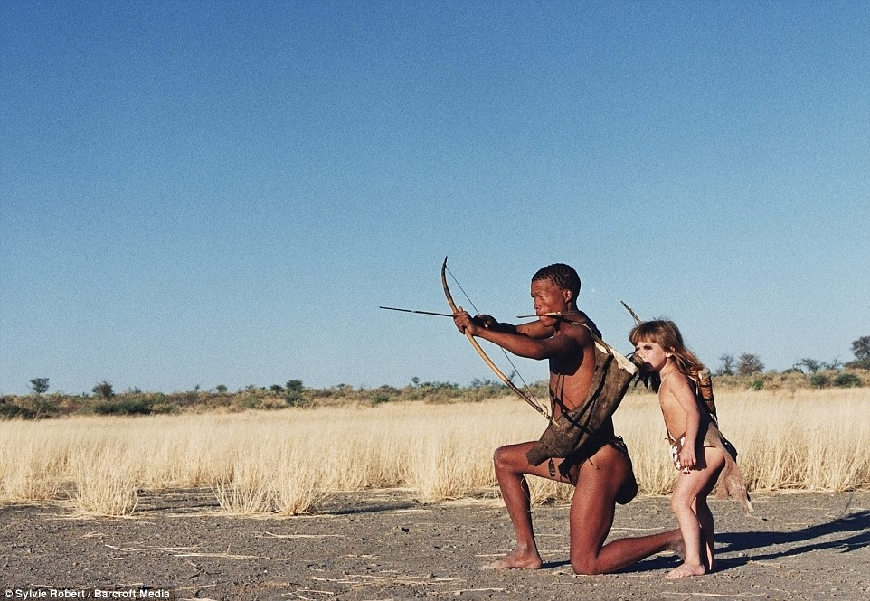 Learning experience: The young girl is pictured with Tkui, of the San Bushmen of northern Namibia in one of the images in the book