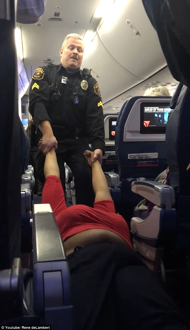 Many of the passengers craned their necks and expressed their shock as they watched police officers struggle to pull her off the plane