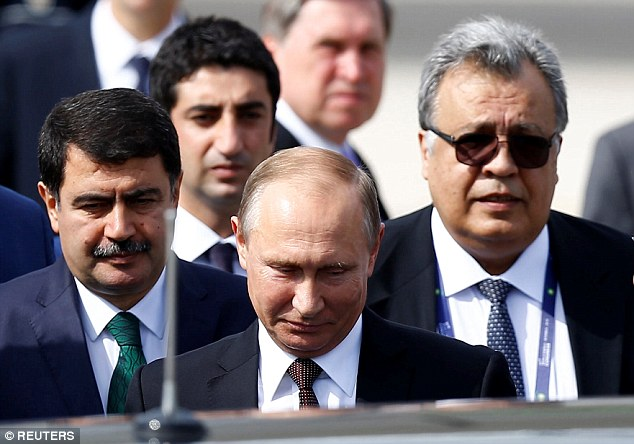 A key ally of Vladimir Putin, centre, has blamed NATO for the murder of the Russian Ambassador to Turkey Andrey Karlov, right, while attending an exhibition in Ankara