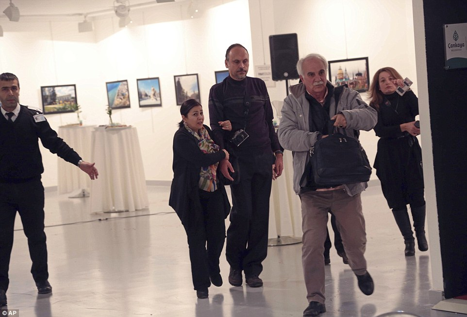 Spectators are evacuated from the gallery after Mr Karlov was shot dead by the Turkish police officer
