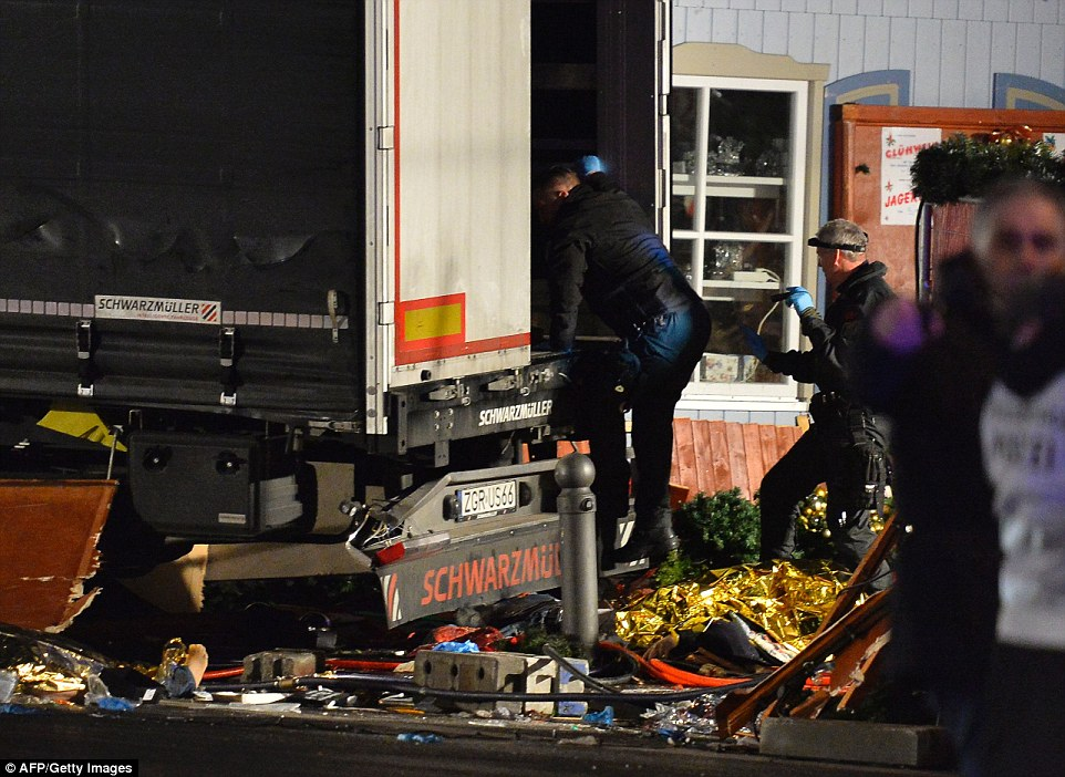 Police detectives climbed over the debris to search the truck, as investigators worked through the night to establish what had happened