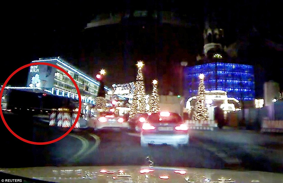 Seconds from disaster: Dashcam footage shows the hijacked truck (circled in red) speeding past waiting cars as it careers towards the pedestrianised street