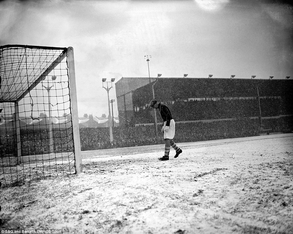 Manchester City goalkeeper Bert Trautmann turns his back on the play as the falling snow is blown into his face