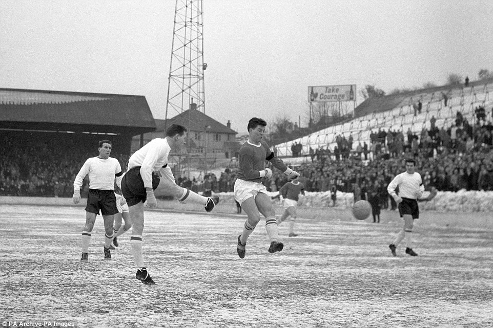 Tony Knapp kicks the ball past Charlton Athletic's outside-left Kinsey (right) in the Second Division match played on Charlton's frozen ground