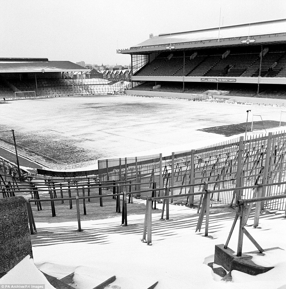 Highbury Stadium was once again covered in snow with a groundsmen clears the penalty area in the far corner of the picture