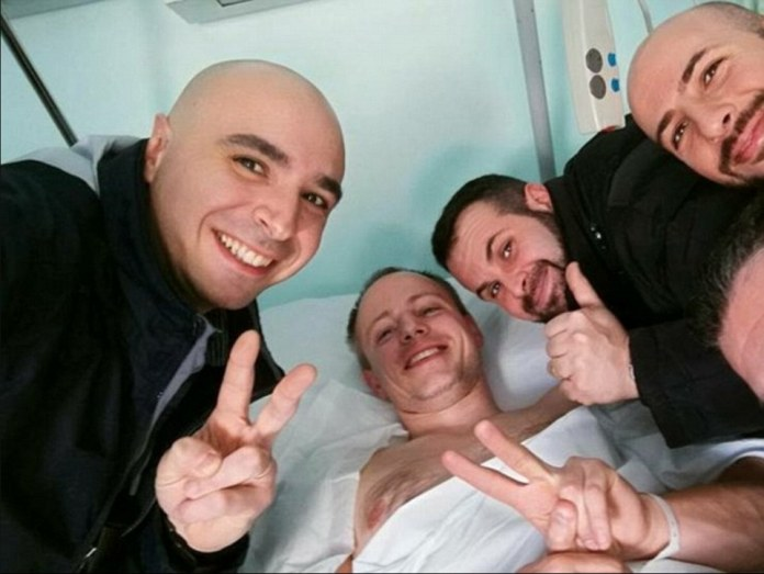 Hero policeman Christian Moveo (pictured in bed) was recovering in hospital this afternoon having been shot by the most wanted man on the planet