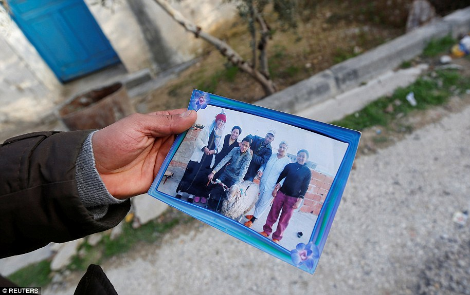 Brother of the Berlin Christmas market truck attack suspect Anis Amri, shows a picture of Anis Amri (centre), in Oueslatia, Tunisia
