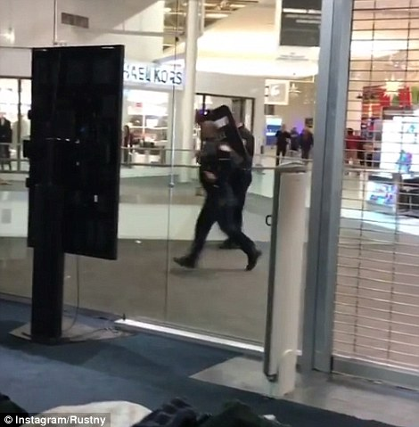 Center under siege: Police with riot shields and body armor raided the mall, while shoppers either ran or hid in stores