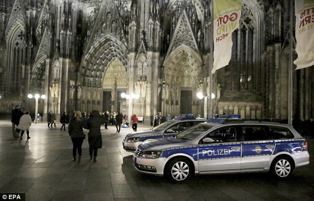 Police cars are pictured outside Cologne's famous cathedral. The authorities are taking no chances this year and are flooding the city with 1,500 police - ten times the number on duty in 2015 - to stop a repeat of the disgraceful scenes last year