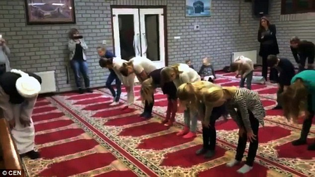The children, who are mainly from Christian backgrounds, are shown how to pray by an imam