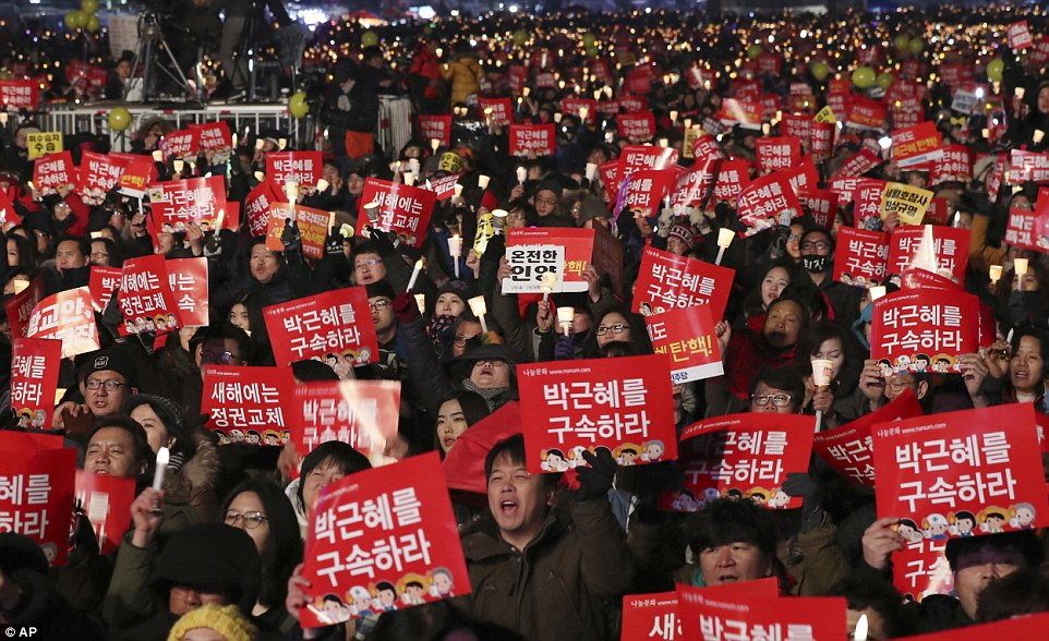 Even on New Year's Eve, protesters shout slogans as they hold signs and candles during a rally demanding the resignation of South Korean President Park Geun-hye in Seoul, South Korea on Saturday