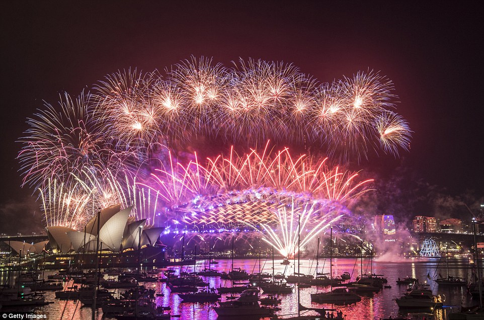 Happy New Year! Pink, purple and orange fireworks explode over the Sydney Harbour Bridge and the Sydney Opera House