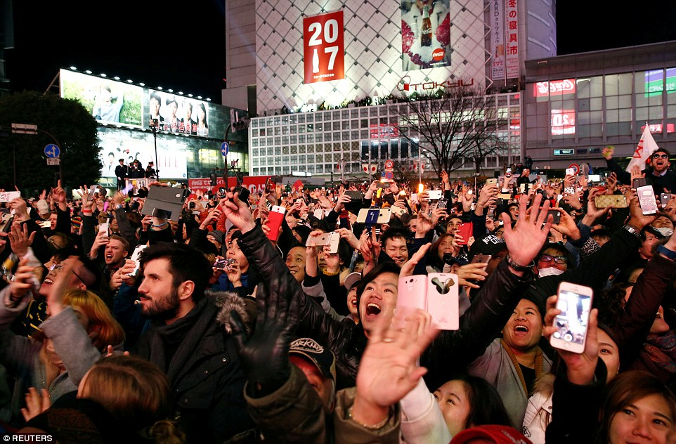 Revellers wave hands as they take part in a new year countdown event at Shibuya crossing in Tokyo, Japan