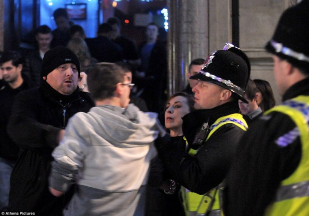 A man with glasses is restrained by bouncers and police outside a club on Wind Street, in Swansea