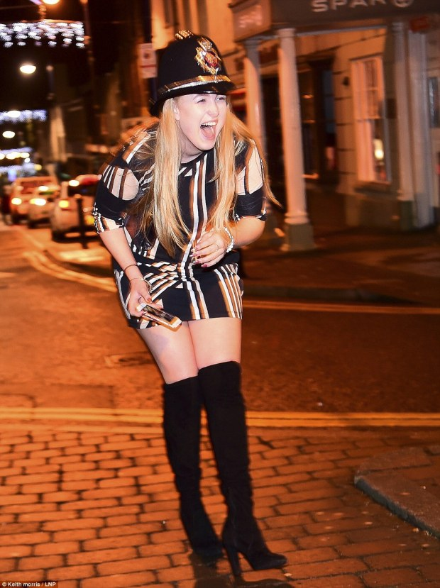 A young woman dressed in a policeman's hat while out celebrating New Year in Aberystwyth, in Wales