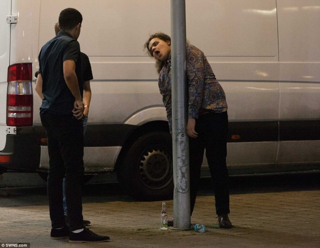 A man in Bristol stands against a lamppost as some celebrated the New Year with a little too much gusto