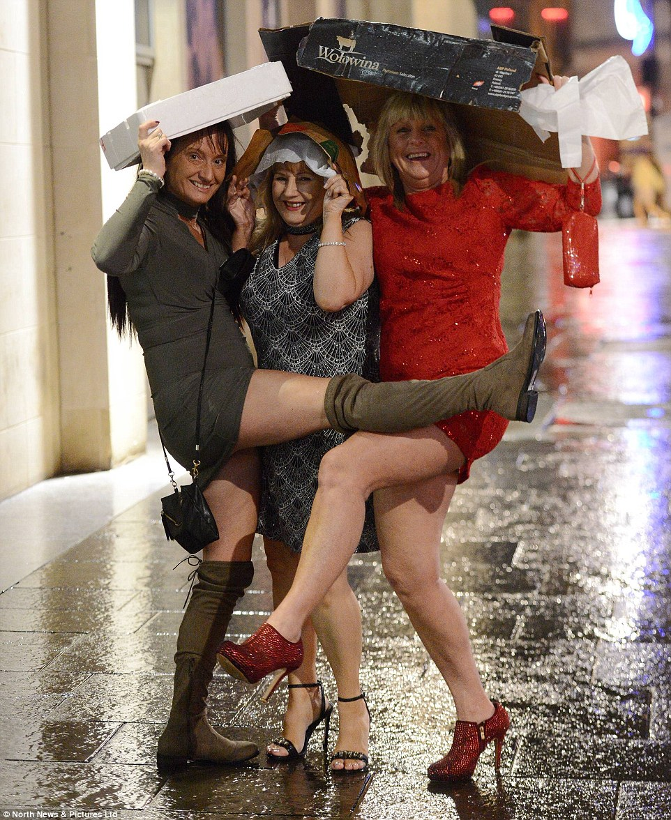 Three women shield their hair during a rain-soaked New Year's Eve celebrations in Newcastle