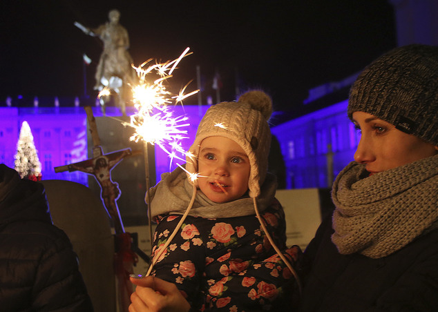 Spectators celebrate the New Year in front of the Presidential Palace in Warsaw, Poland, Sunday, Jan. 1, 2017. Thousands of Warsaw residents took to the stre...