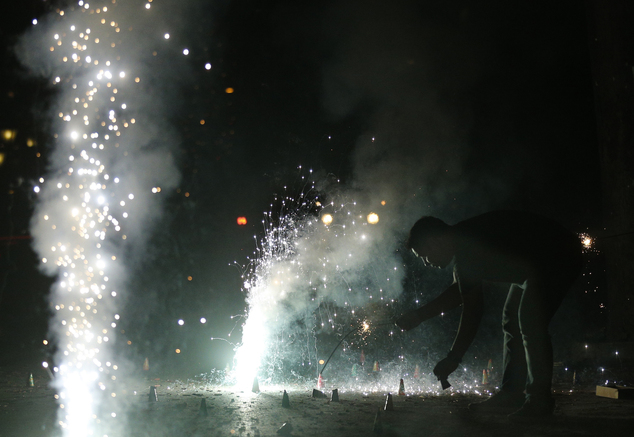 An Indian man lights firecrackers on the street during the New Year celebration in Mumbai, India, Sunday, Jan. 1, 2017. (AP Photo/Rafiq Maqbool)