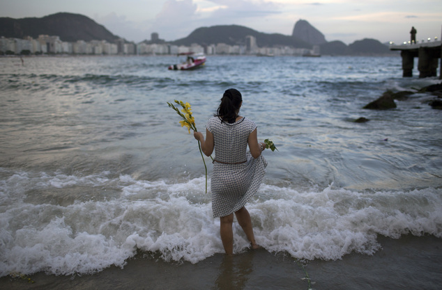 A woman offers flowers to Yemanja, goddess of the sea, for good luck in the coming year during New Year's Eve festivities on Copacabana beach in Rio de Janei...