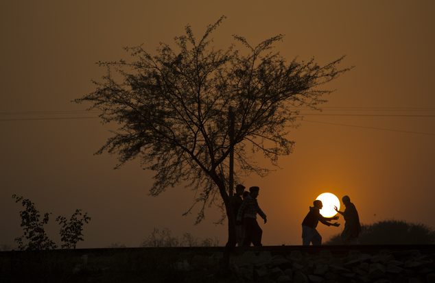 Children displaced from Pakistani tribal areas due to fighting between security forces and militants play under a tree during the last sunset of the year on ...