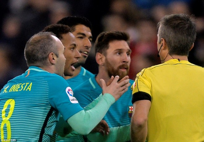 Andres Iniesta is booked as he protests alongside Neymar, Suarez and Messi after Barcelona are denied a penalty