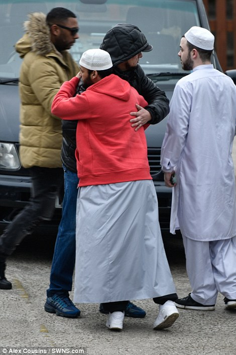 Two friends hug outside the mosque before the short funeral this morning