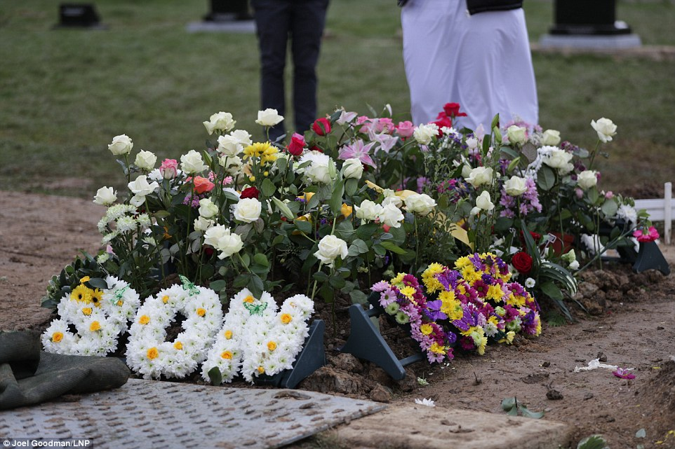 Laid to rest: Yassar Yaqub was buried in Huddersfield in a grave covered in roses and with flowers spelling 'Yas', 'Son' and 'Dad'